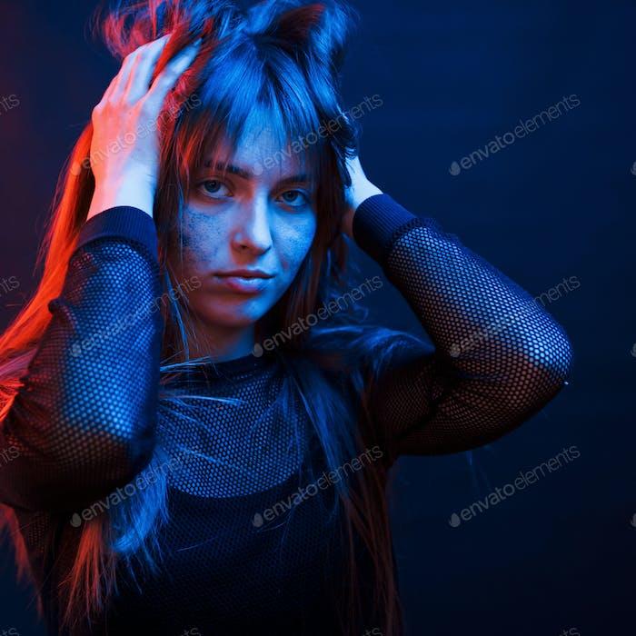 Beautiful haircut. Studio shot in dark studio with neon light. Portrait of young girl