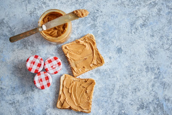 Two tasty peanut butter toasts placed on stone table
