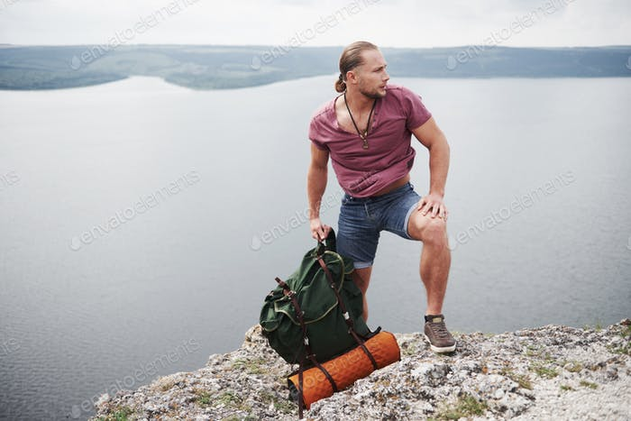 Traveller with backpack sitting on top of mountain enjoying view above the water surface