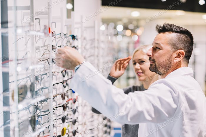 Optician and his patient choosing glasses.