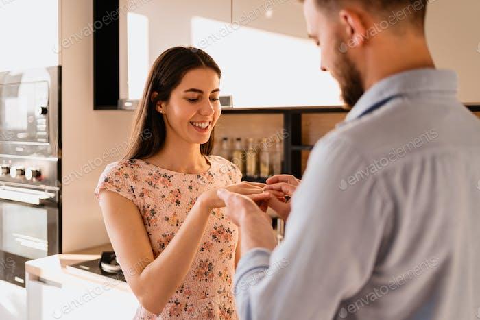 El hombre pone el anillo en su dedo novias