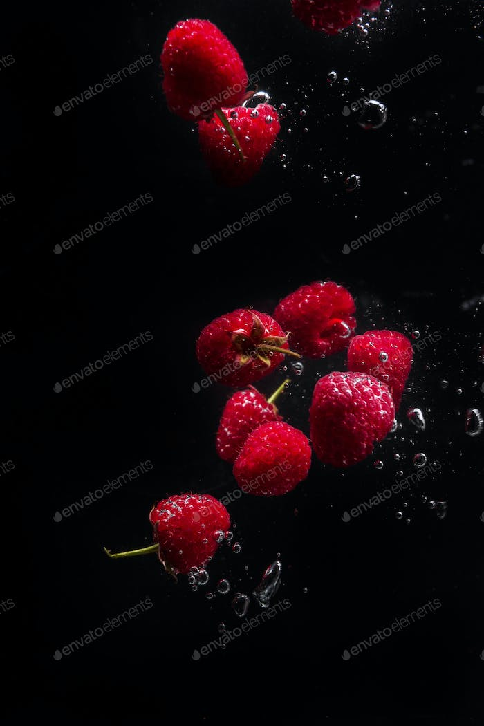 Raspberries falling in water  on a black background.