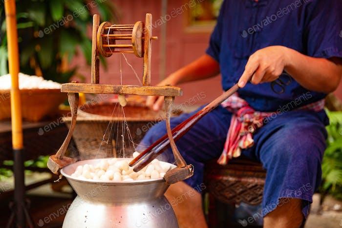 Mann Abwickeln Seide von Kokons in großen Hot Pot