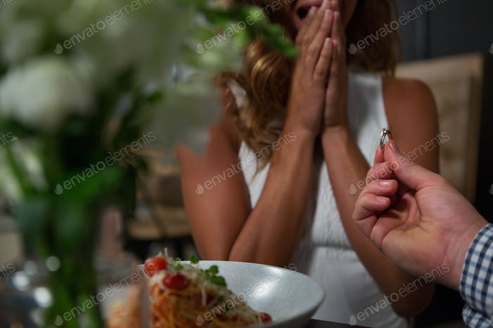 Man proposing woman while dining