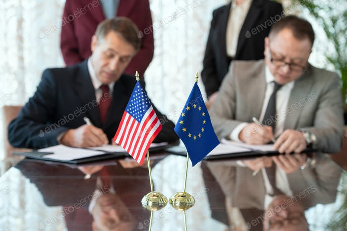 Flags of United States and European Union on table against two delegates