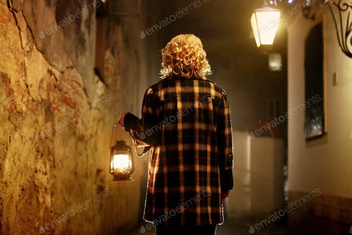 Beautiful blonde female detective with vintage lantern in retro coat walking in old street