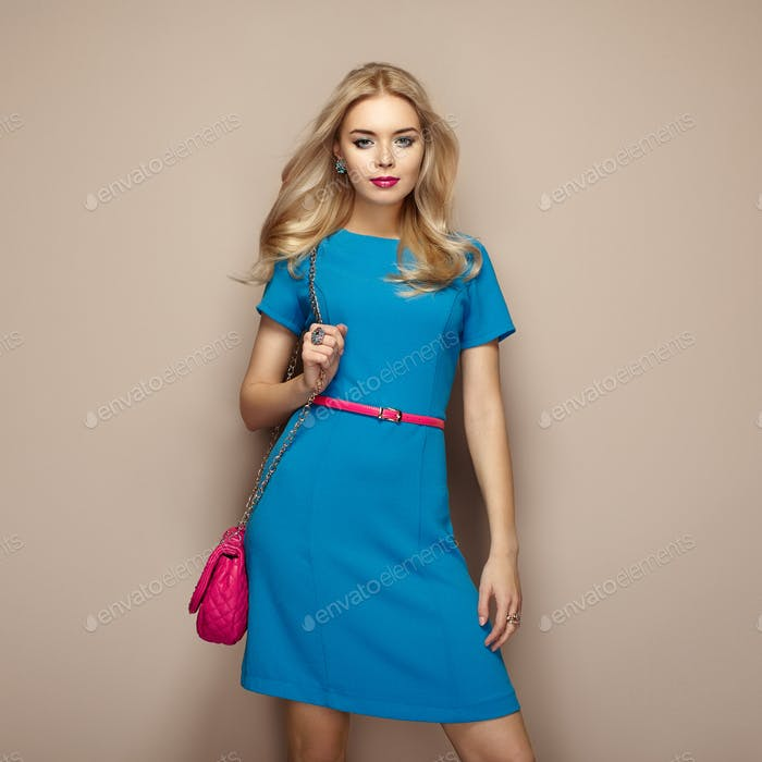 Blonde young woman in elegant blue summer dress