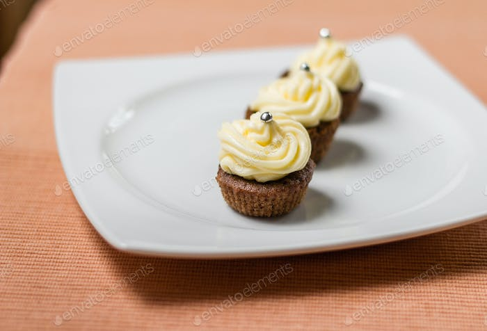 Chocolate cupcakes with silver sprinkles on top on white plate