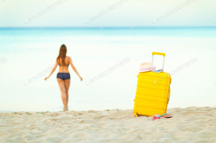 Yellow suitcase on the beach and a girl walks into the sea in th