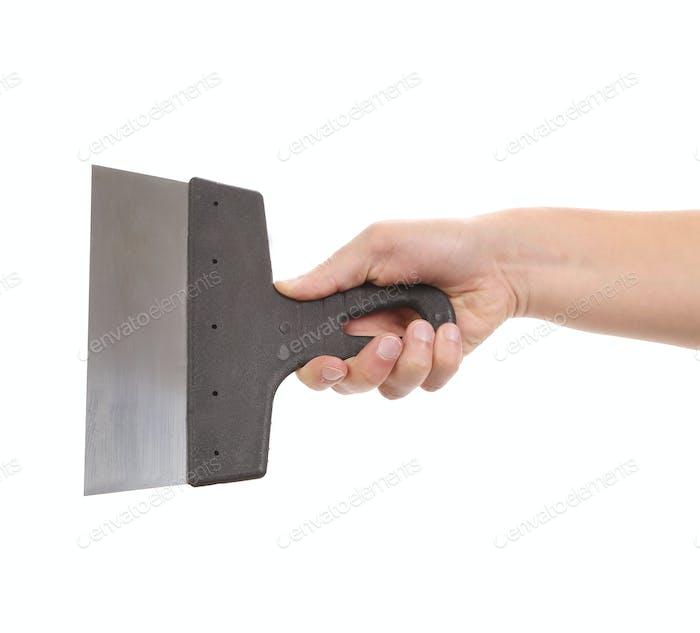 Hand holds construction spatula.