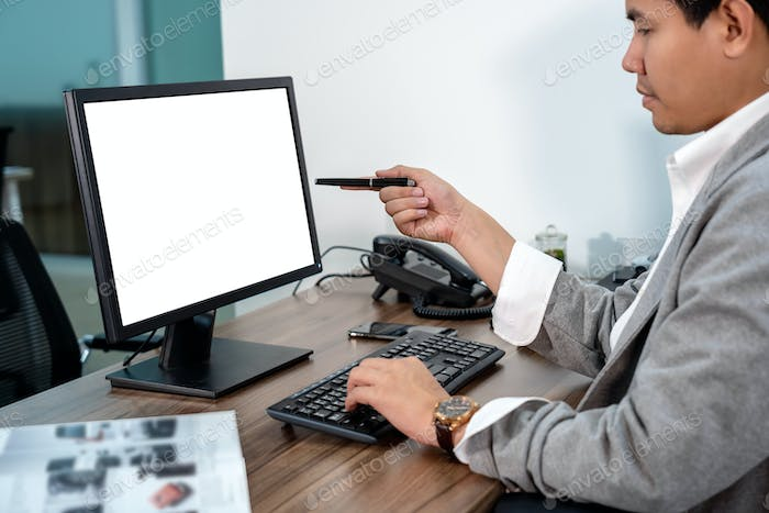 Asian Businessman in formal suit using and pointing the pen to computer screen in office