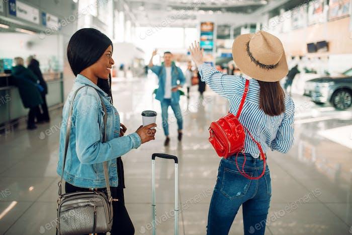 Zwei weibliche Touristen treffen einen Freund am Flughafen