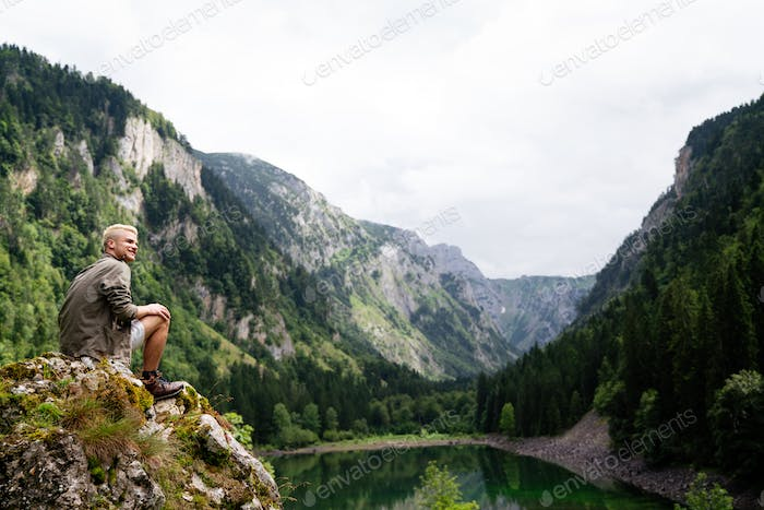 Hiker with backpacks reaches the summit of mountain peak. Success, freedom and happiness concept