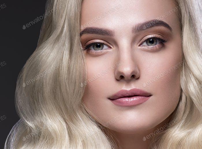 Blonde Hair Woman Beautiful Curly Hairstyle Wavy Long hair Natural Make up. Studio shot. On black