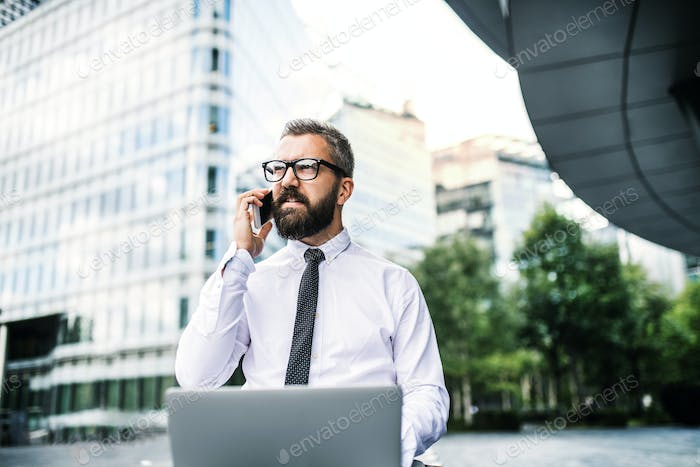 Hipster businessman with laptop and smartphone in the city.