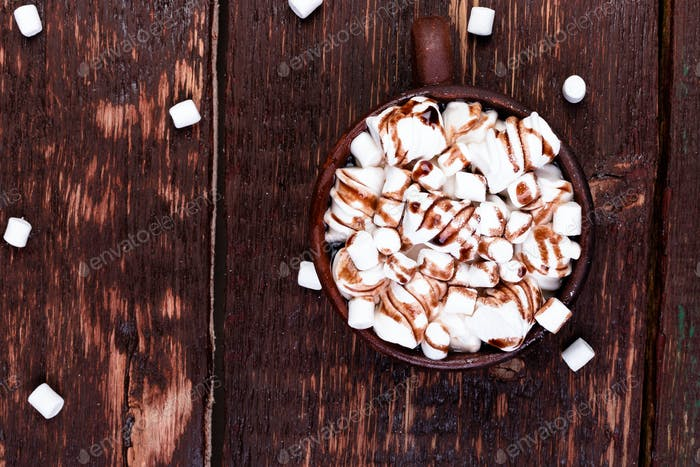 Hot chocolate with marshmallow in brown cup on wooden background. Copy space.