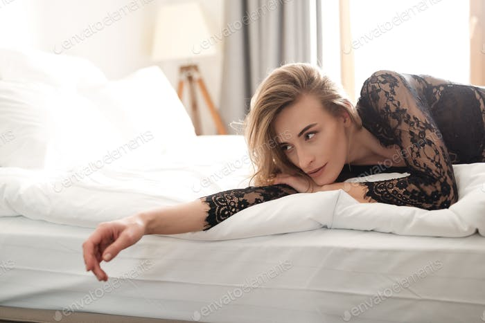 Brünette sexy Frau liegt auf Bett drinnen gekleidet in Dessous
