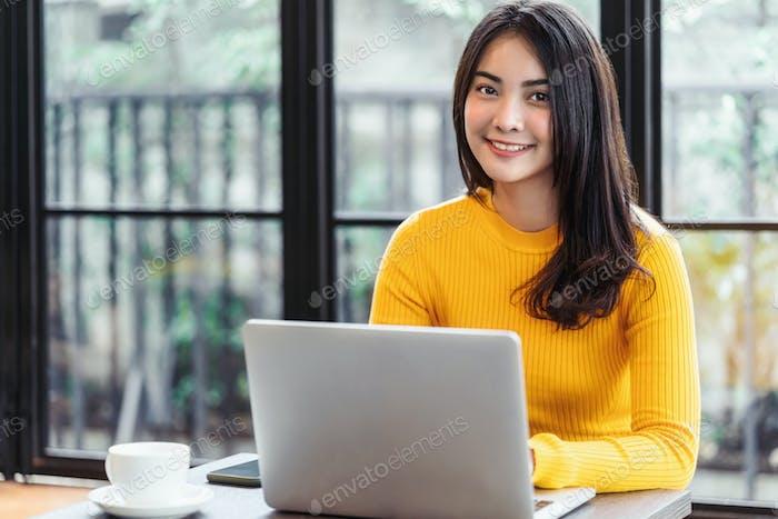 Junge Asiatin arbeitet mit Laptop für Online-Shopping im Café oder Coworking Space