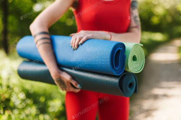 Close up photo of young woman body in red jumpsuit standing with colorful yoga mats in hands in park