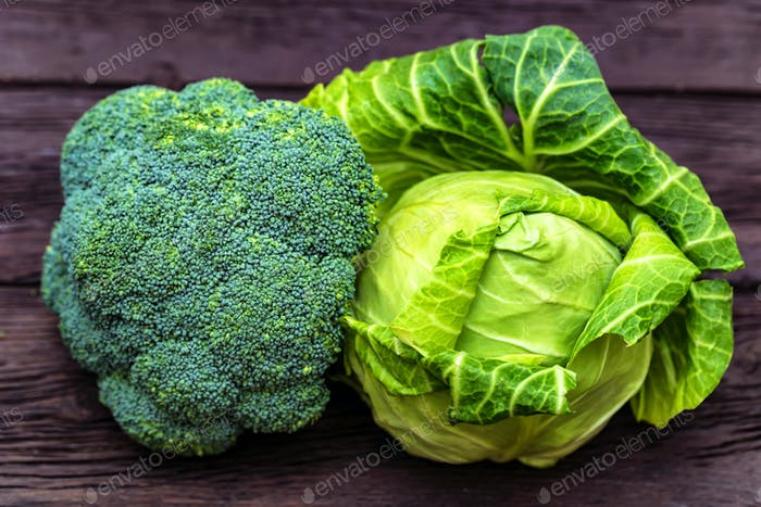 Green fresh broccoli and cabbage on wooden surface