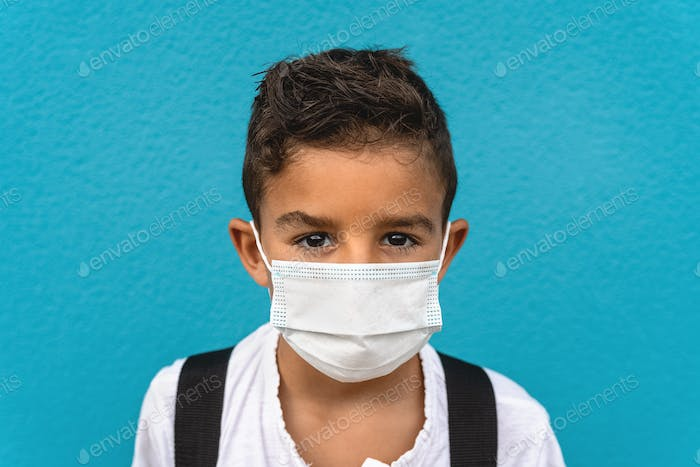 Child wearing face protective mask going back to school during corona virus pandemic