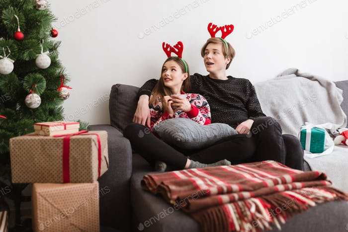 Teen couple sitting on sofa wearing deer horns while dreamily looking at Christmas tree