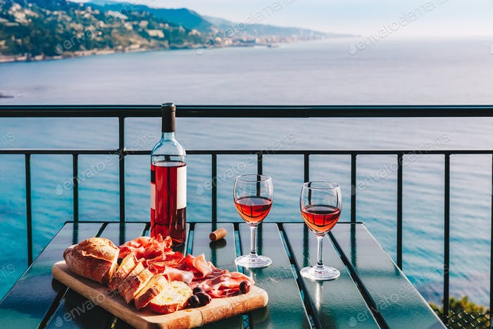 Two glasses of wine and italian snacks  with amazing view at sunset in Italy.