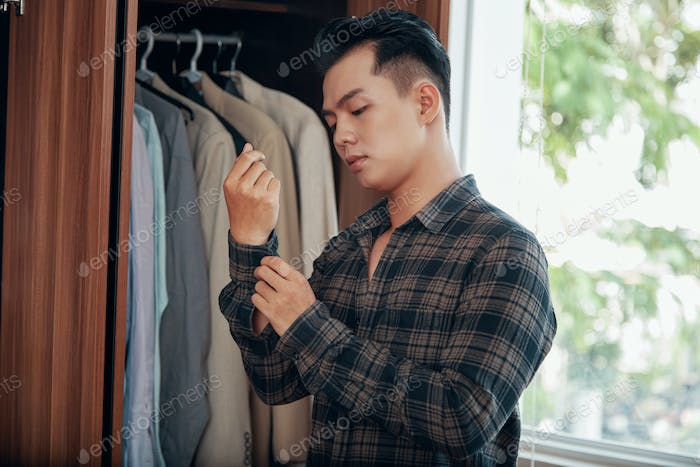 Casual man getting dressed in morning time