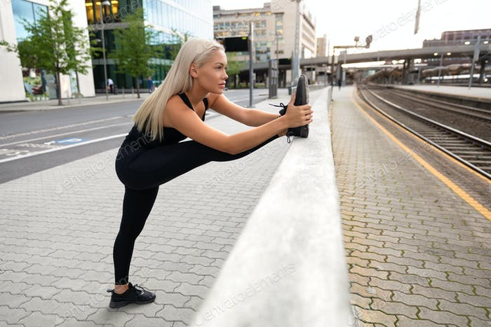 Perfect looking Urban Female Stretching Her Leg Before Exercise