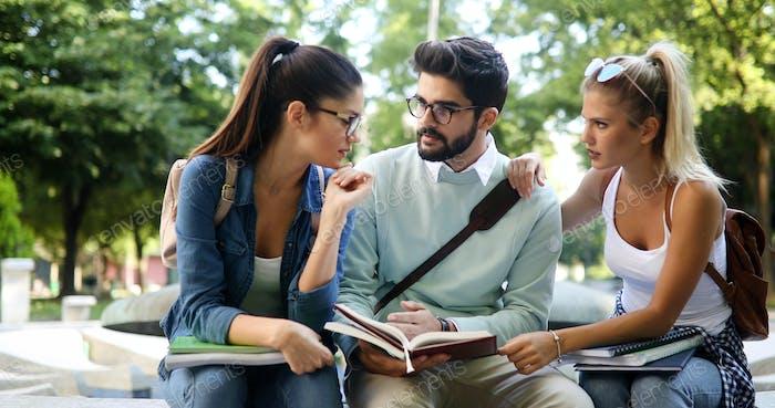 Alegre jóvenes estudiantes universitarios Amigos estudiando con libros en la universidad