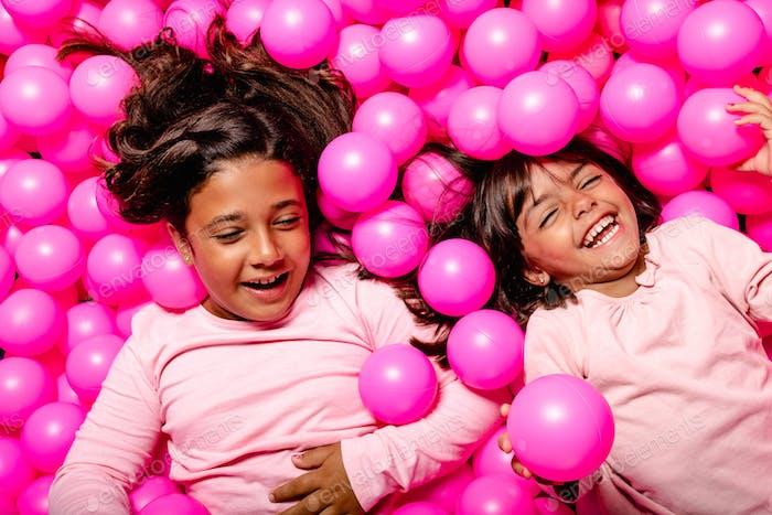 zwei kleine Mädchen lächelnd und spielen am rosa Ball Pool
