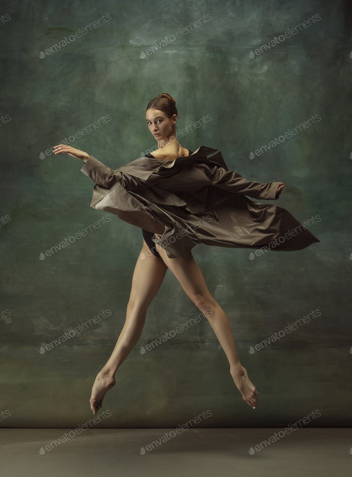 Young graceful tender ballerina on dark studio background