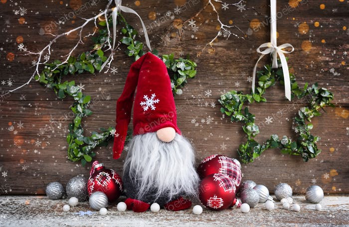 Christmas composition with gnome and festive decorations on wooden background