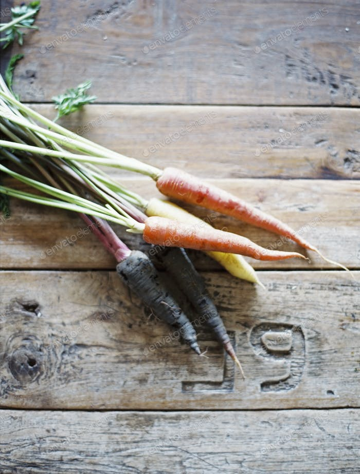 A domestic kitchen table with a worn scrubbed surface. A bunch of fresh carrots.