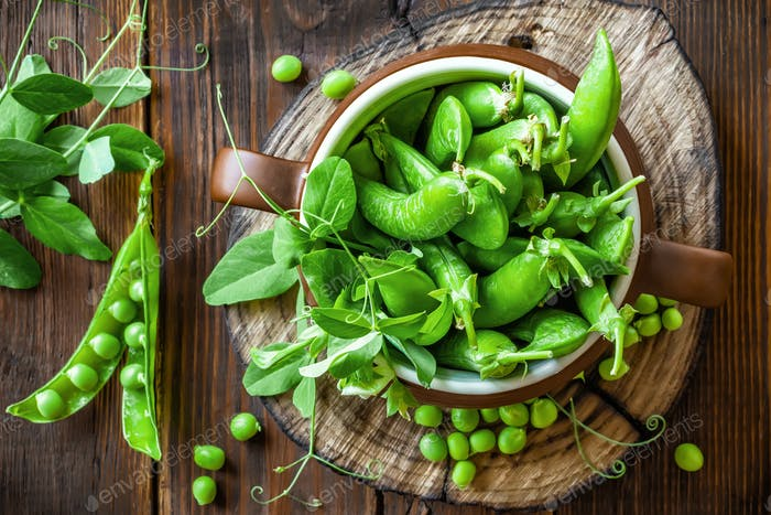 Fresh green peas on dark wooden rustic background