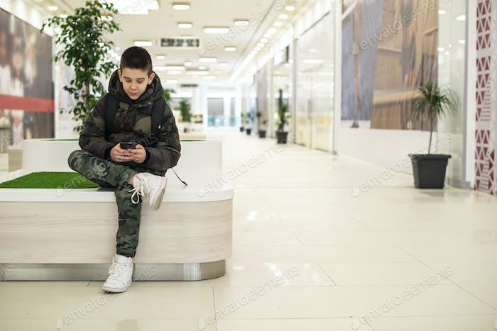 Teenager playing with smartphone in modern commercial center. Te
