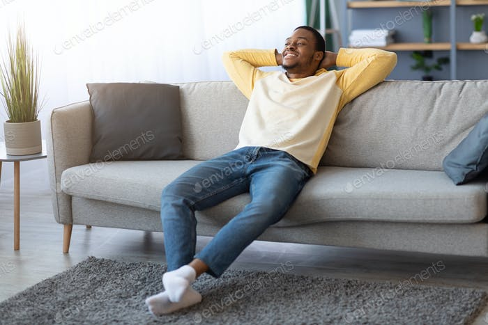 Carefree black guy relaxing on couch at home