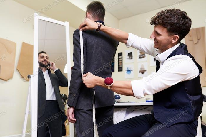 Tailor Measuring Male Model in Atelier