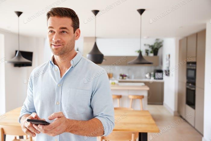 Mann mit App auf dem Smartphone zur Steuerung der Zentralheizung Temperatur im Haus