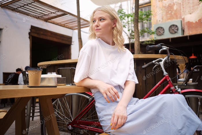 Beautiful casual blond girl thoughtfully looking away resting alone in courtyard of cafe