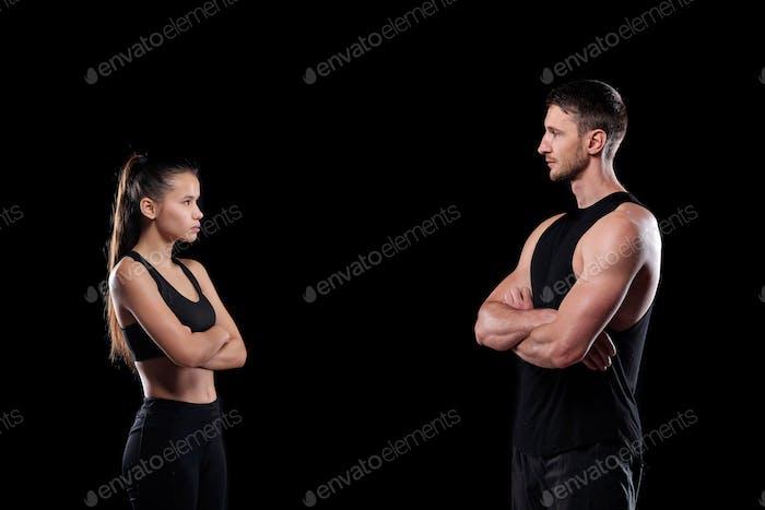 Deportista joven y deportista con los brazos cruzados de pie uno frente al otro