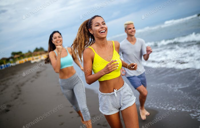 Group of athletes running on ocean front. Friends in sportswear training together outdoors