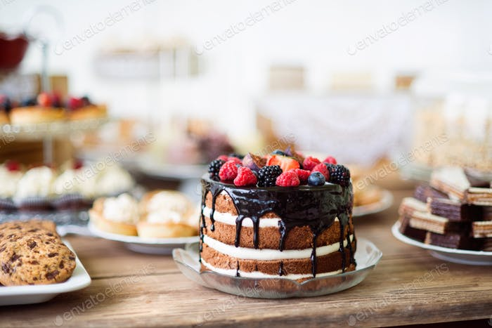 Naked cake with chocolate and berries, cookies and tarts