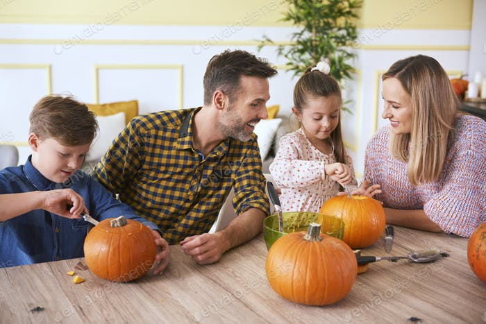 Children carving pumpkins with parents