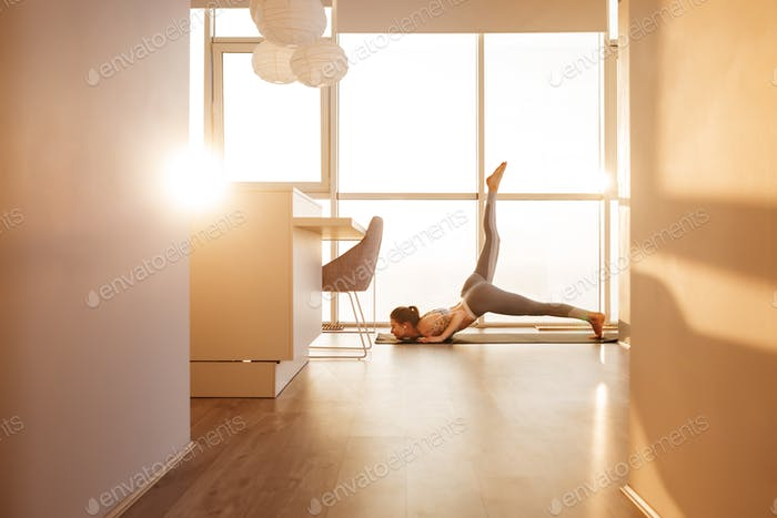 Young lady practicing yoga poses on yoga mat at home with big beautiful windows on background