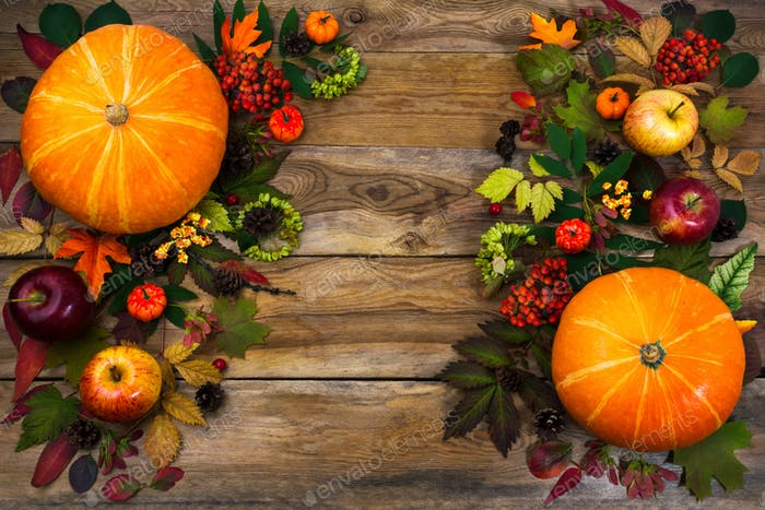 Thanksgiving greeting with leaves and pumpkin on wooden table