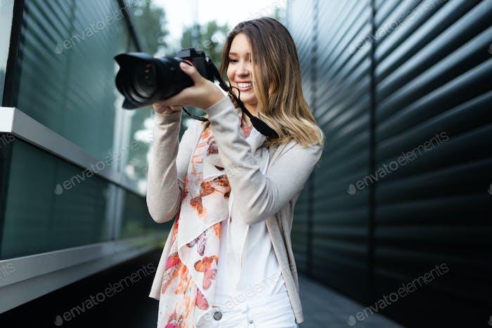 Frau ist ein professioneller Fotograf mit DSLR-Kamera, Outdoor und Sonnenlicht