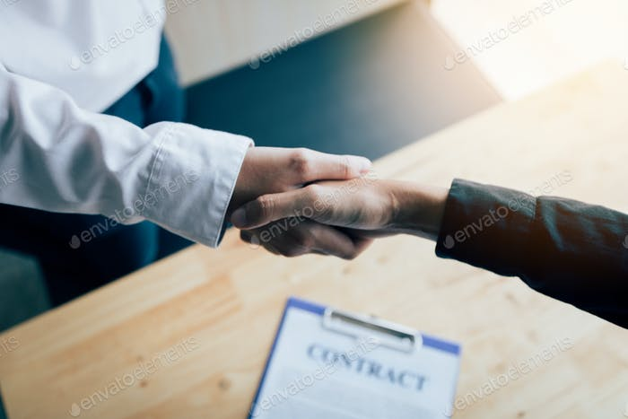 Two people shaking hands with making a contract in the office.