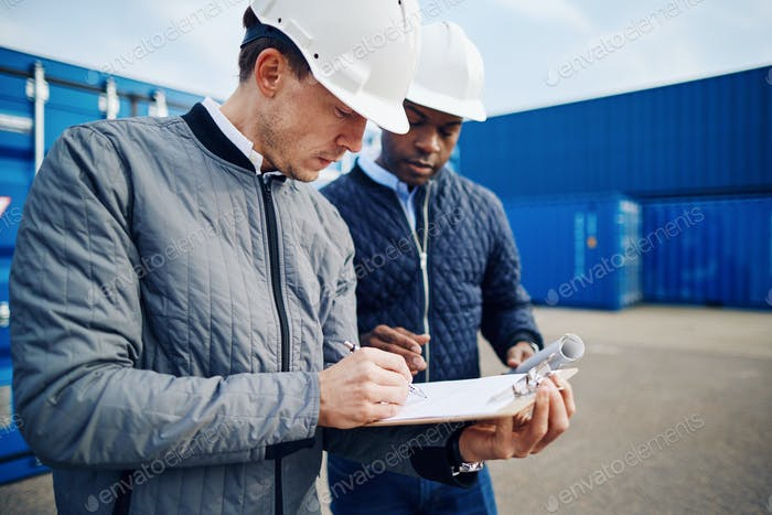 Two engineers standing in a commercial shipping yard tracking containers