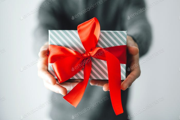 Man holding gift with red ribbon